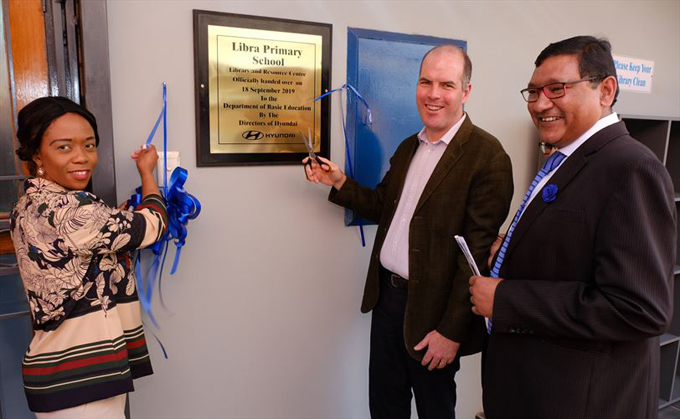 Ms Yvonne Tshepo Mosadi (left), human resources director of Hyundai Automotive South Africa, and Mr Niall Lynch (middle), CEO of Hyundai Automotive SA, unveils the plaque at the entrance of the new library that the company handed over to Libra Primary School in Lenasia. On the right is Mr Tyron Singaram, principal of Libra Primary School.